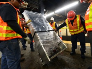 MTA New York City Transit Infrastructure crew installs a new On The Go (OTG) kiosk on the northbound platform at Chambers St on the 7th Av line .